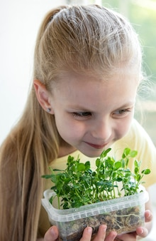 Маленькая девочка у окна наблюдает, как растет микрозелень