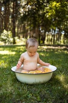 Маленькая девочка купается в белом тазе с апельсинами на природе