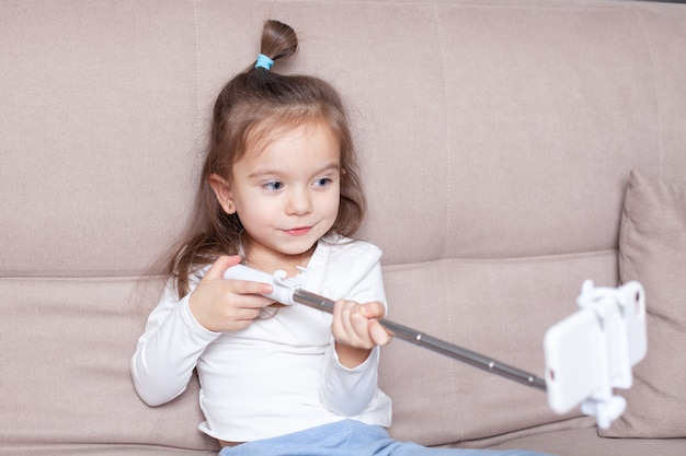 小さな女の子のブロガーが、電話と一脚を使用して加入者向けのライブストリームを実施しています