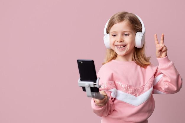 어린 소녀 블로거 인플 루 언서가 스마트 폰으로 블로그의 동영상을 녹화하고, 구독자와 소통하고, 셀카를 찍고, 헤드폰으로 음악을 듣고, 원격으로 학습합니다.