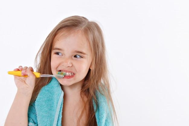Маленькая девочка чистит зубы на белом фоне. портрет ребенка с желтой зубной щеткой. синее полотенце на шее. утренние гигиенические процедуры