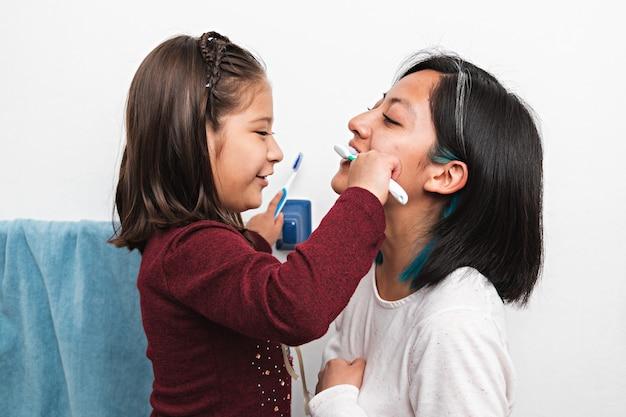화장실에서 젊은 여자의 이를 닦는 어린 소녀