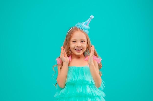 小さな女の子がスタジオターコイズの背景で彼女の誕生日を祝う