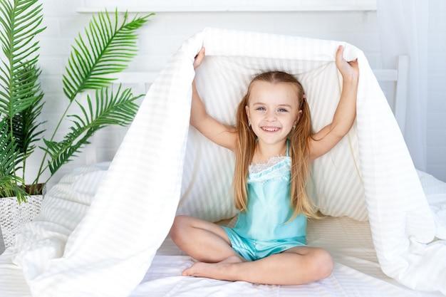 Маленькая девочка играет под одеялом, просыпается утром дома на кровати на белой хлопчатобумажной кровати и сладко улыбается.