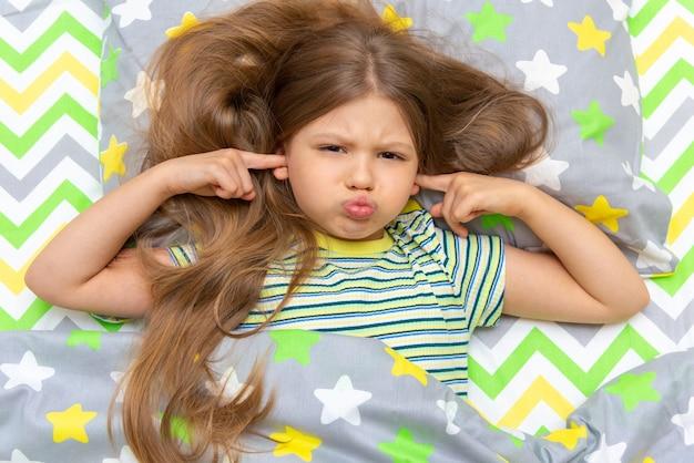目覚まし時計のせいで、ベッドに横になっている少女が指で耳をふさいだ。