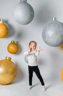 거대한 크리스마스 공을 들고있는 마법사를 묘사 한 어린 소녀