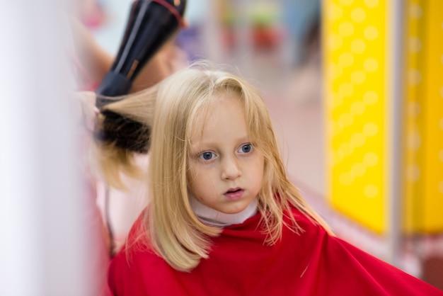 Маленькая девочка делает стрижку.