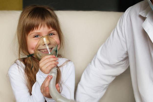 小さな女の子が家でスプレーで吸入します、医者が近くにいます。喘息吸入ネブライザー蒸気病咳の概念からの子供のための吸入器。