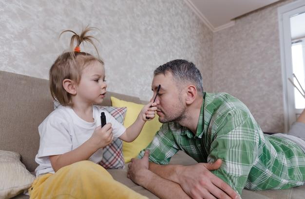 Маленькая девочка делает макияж своему отцу во время совместных игр