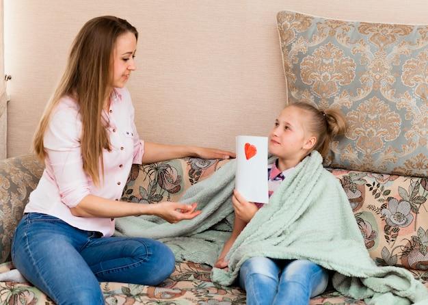 小さな女の子が母の日に「お母さん、愛してる」という言葉でお母さんのグリーティングカードを描きます。女の子は心で描くお母さんを示しています