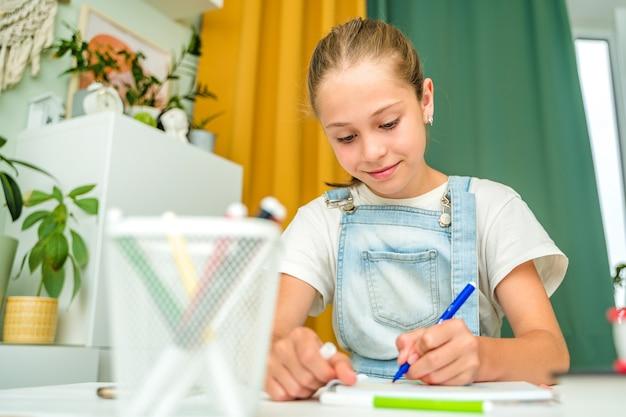 어린 소녀는 현대적인 거실에서 집에서 펠트 펜으로 그림을 그립니다.