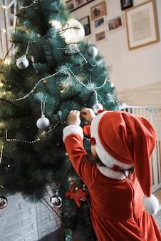 산타 클로스 옷을 입은 어린 소녀가 크리스마스 트리를 장식하고 있습니다.