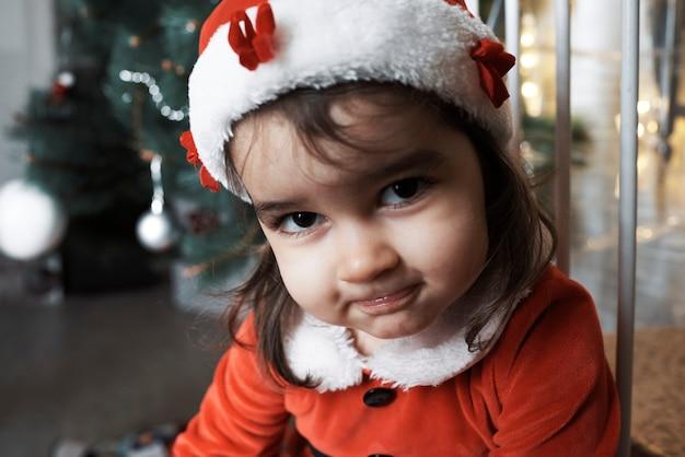 산타 클로스 옷을 입은 어린 소녀가 미소를 지으며 카메라를 들여다 본다.