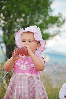 Маленькая девочка, пить из бутылки на открытом воздухе