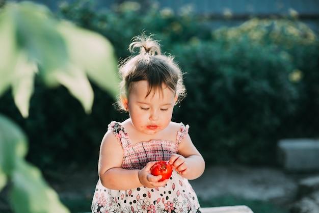 토마토를 먹는 어린 소녀. 혼자서 정원에서 아주 귀여운 백라이트