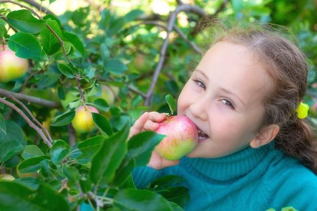 어린 소녀가 정원에 있는 사과나무 아래에서 사과를 먹고 있다