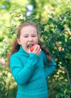어린 소녀는 사과를 먹는다
