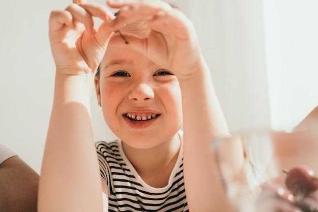 Маленькая девочка ест вишню ребенку в солнечный день в полосатой футболке крупным планом портрет маленького ...