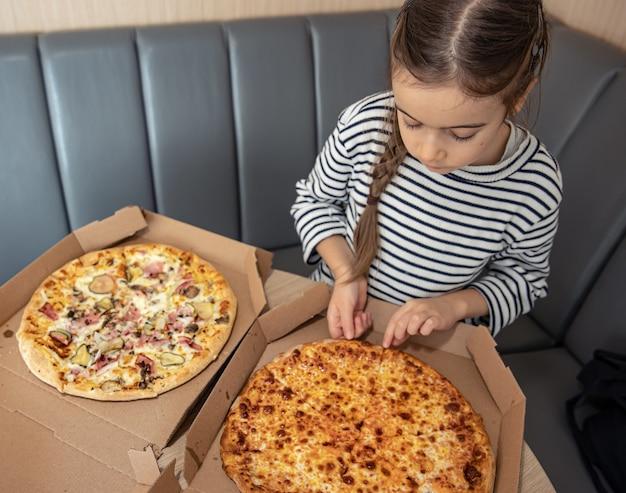 한 어린 소녀가 점심으로 피자를 먹고 최고의 조각을 선택합니다.