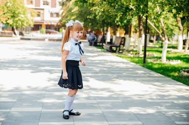 小学生の女の子が通りを歩いて楽しんでいます。子供は楽しく学校に行きます。学校に戻ります。