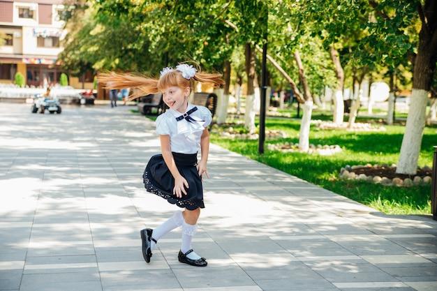 Маленькая девочка начальной школы весело гуляет по улице. ребенок с радостью ходит в школу.