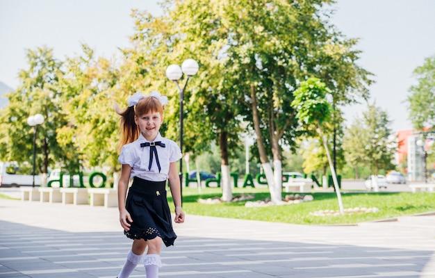小学生の女の子が通りを歩いて楽しんでいます。子供は楽しく学校に通っています。