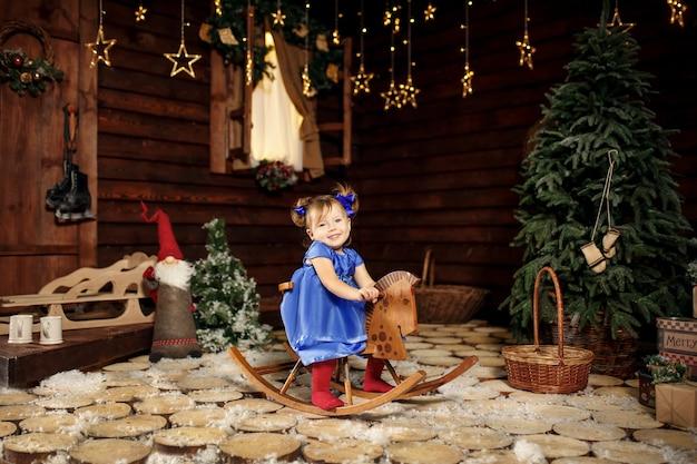 小さな女の子は、クリスマスに彼女に与えられたロッキングホースに乗ることを楽しんでいます