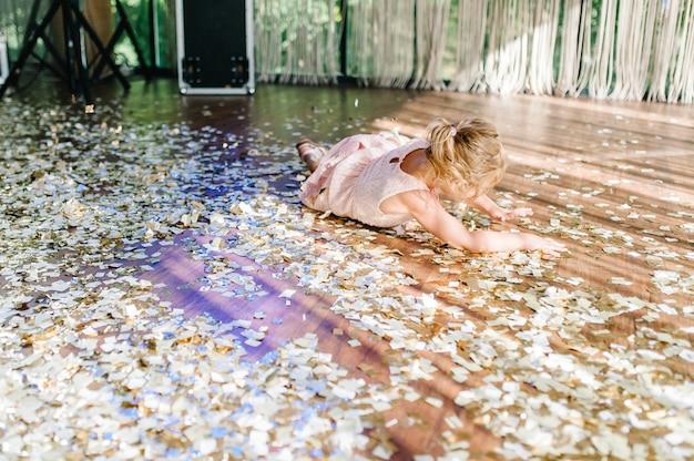 Маленькая девочка упала на пол на бумажное конфетти. много конфетти во время вечеринки на сцене. красочное шоу с золотым конфетти.