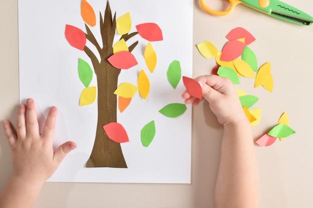 Маленькая девочка приклеивает листья на деревце из цветной бумаги. детское творчество. планировка квартиры, вид сверху