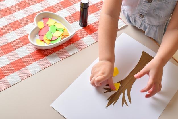 Маленькая девочка приклеивает листья на деревце из цветной бумаги. детское творчество.