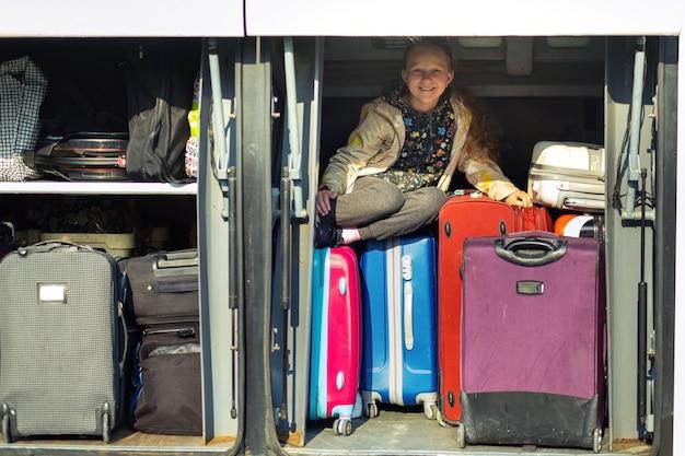 小さな女の子がスーツケースを持ってバスの貨物室に隠れました。