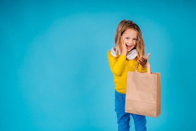 小さな女の子がカメラを見て集めた紙袋を持っています。