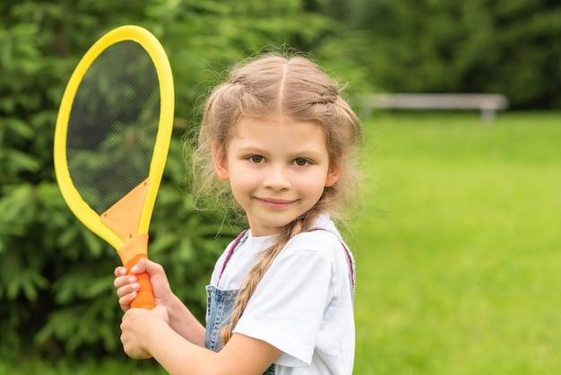 Маленькая девочка держит детскую теннисную ракетку.