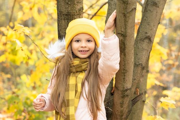 秋の朝、木を握っている少女。