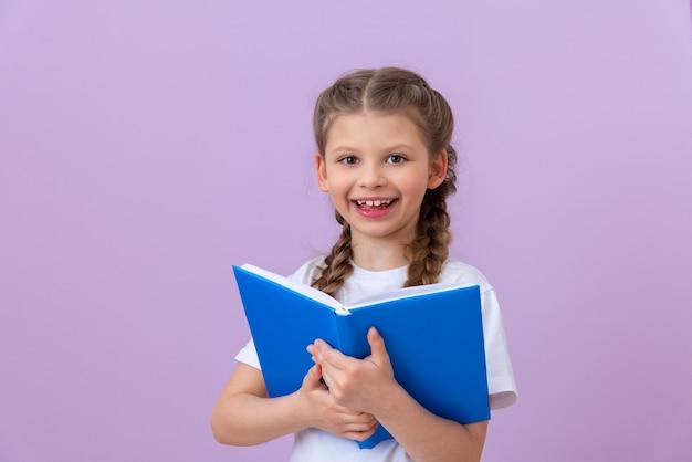 小さな女の子が本を持って幸せです。