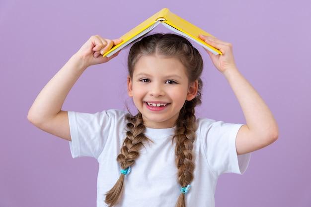 小さな女の子は紫色の背景に彼女の頭の上に屋根のような本を持っています