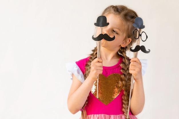 어린 소녀가 아버지의 날을 위해 카니발 콧수염, 모자, 안경을 들고 있습니다.