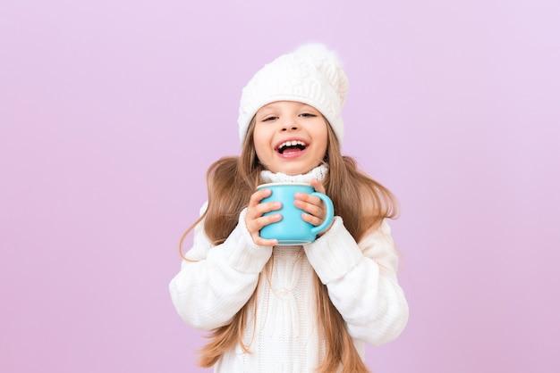 어린 소녀는 뜨거운 음료수 한 잔을 들고 미소를 짓고 있습니다.