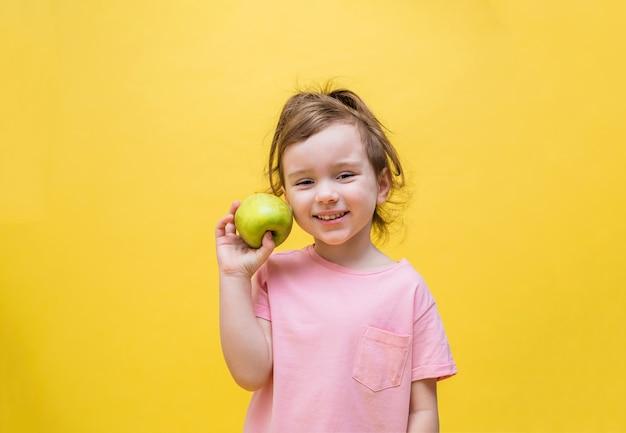 Маленькая девочка держит зеленое яблоко на желтом пространстве. милая девушка с хвостиком улыбается и смотрит. копировать пространство
