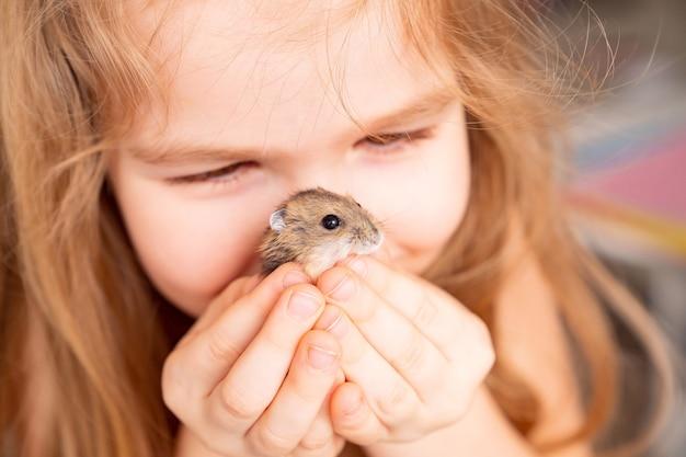 Маленькая девочка держит хомяка перед ее лицом. детская дружба с домашними животными