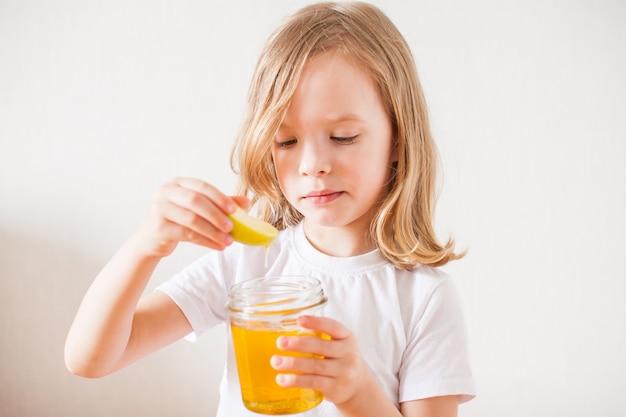 Маленькая девочка держит в руках банку меда и кусочек яблока