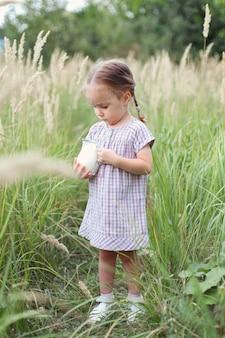어린 소녀는 신선한 우유 한 병을 손에 들고 소박한 생활 방식, 자연, 여름날 산책을 합니다.