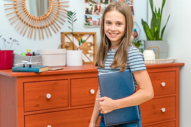 Маленькая девочка держит в руках ноутбук в своей современной комнате дома