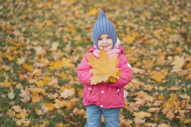 Маленькая девочка держит в руках осенний кленовый лист яркое осеннее фото в парке с листьями ...