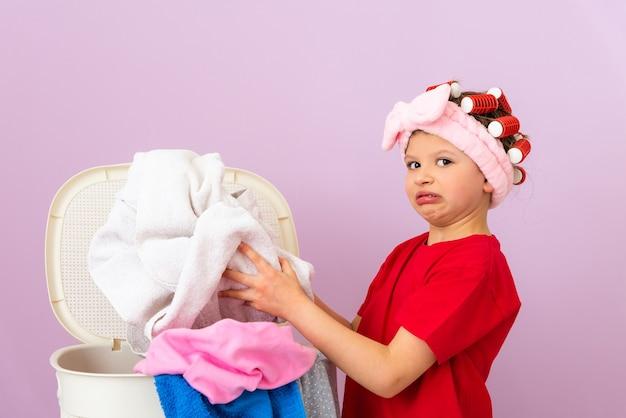 小さな女の子がバスケットから汚れた下着を持っています。家の掃除。
