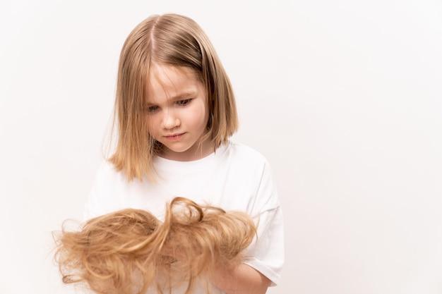 Маленькая девочка держит в руках подстриженные волосы после стрижки на белом фоне. средство по уходу за детскими волосами. детский салон красоты.