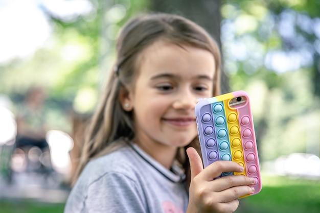 어린 소녀는 트렌디한 안티 스트레스 장난감인 여드름이 터지는 케이스에 전화기를 들고 있습니다.