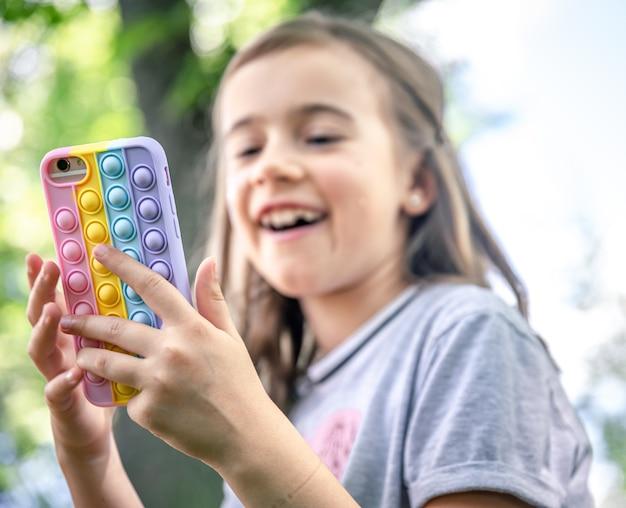 Маленькая девочка держит в руке телефон в чехле с прыщами, модную антистрессовую игрушку.