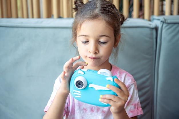 어린 소녀는 즉석 사진 인쇄를 위해 아이들을 위한 파란색 장난감 디지털 카메라를 손에 들고 있습니다.