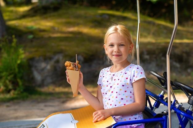 어린 소녀는 뿌리와 과자와 함께 와플에 맛있고 아름다운 아이스크림을 손에 들고 있습니다.
